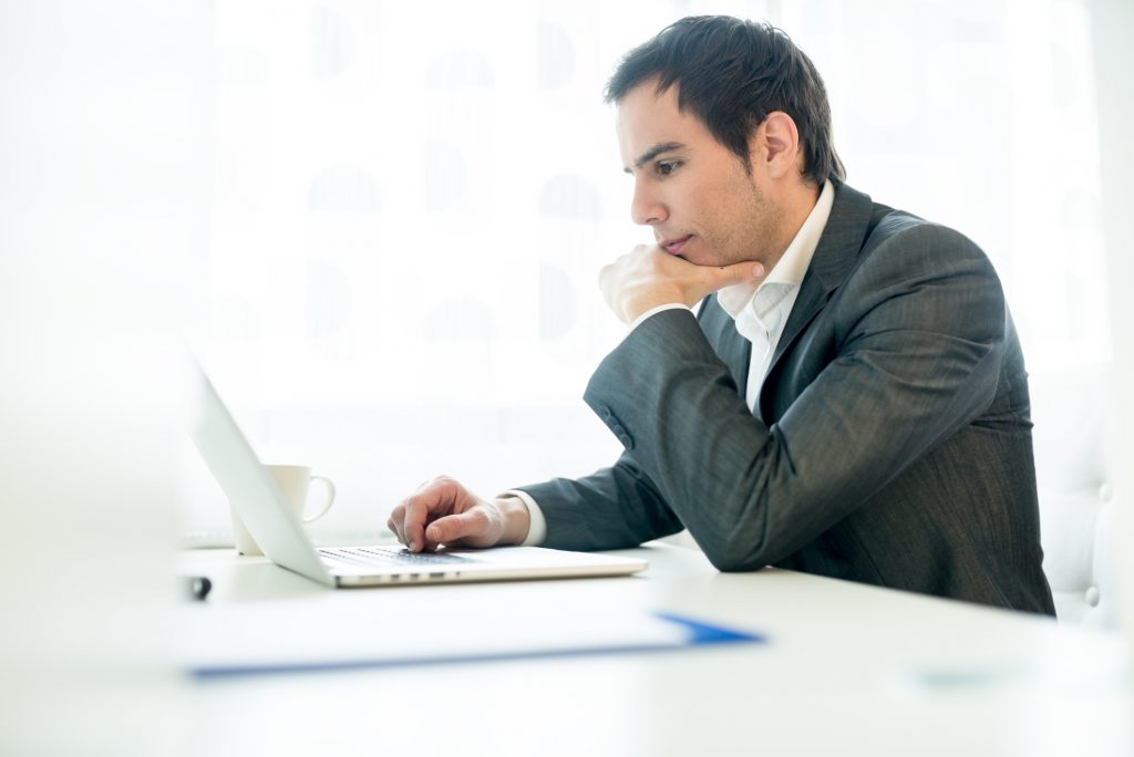 Serious young businessman concentrating on his work as he sits at his desk leaning on one arm navigating the internet on his laptop computer while reading the screen, profile view.