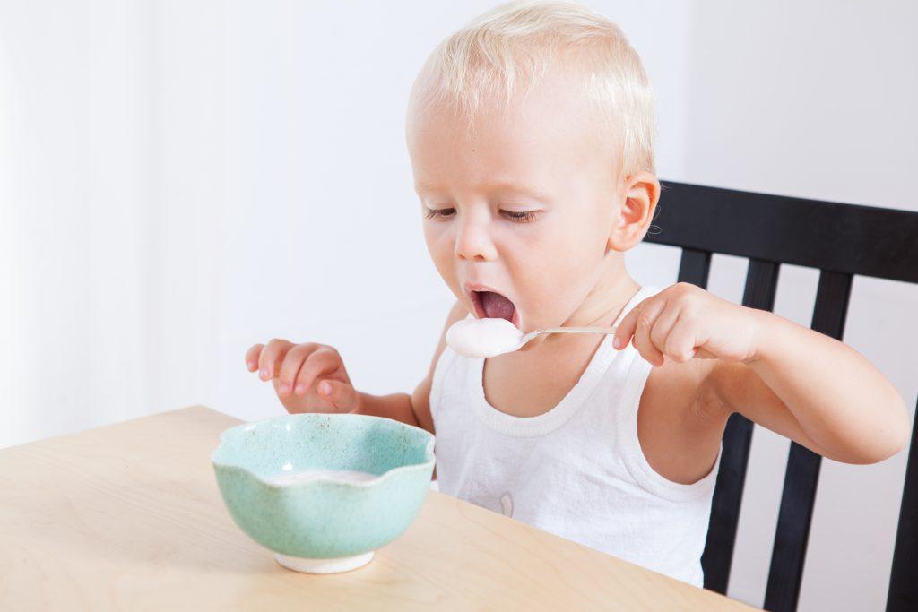 Little cute child boy eating yogurt himself, morning breakfast