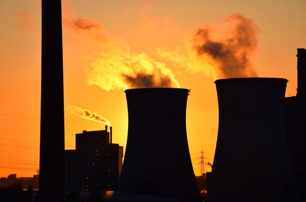 Silhouette of the plant smokestack polluting the air